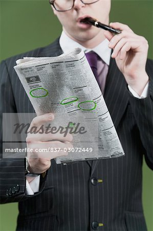 Close-up of a businessman marking on a newspaper Stock Photo - Rights-Managed, Image code: 837-03072449