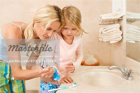 Woman helping her daughter in brushing teeth Stock Photo - Rights-Managed, Image code: 837-03073745
