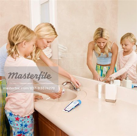 Woman helping her daughter in brushing teeth Stock Photo - Rights-Managed, Image code: 837-03074270