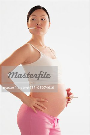 Pregnant woman holding a cigarette on her abdomen Stock Photo - Rights-Managed, Image code: 837-03074616