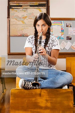 Schoolgirl playing a clarinet in a classroom Stock Photo - Rights-Managed, Image code: 837-03074735
