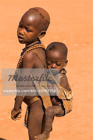 Young Hamer girl carries her baby sister on her back in a goat skin baby carrier, Dombo village, Turmi, Lower Omo valley, Ethiopia, Africa Stock Photo - Rights-Managed, Image code: 841-02707359