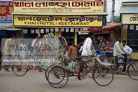 Men riding cycle rickshaws on the street passing the outside of a hotel and restaurant in the city of Dhaka (Dacca), Bangladesh, Asia Stock Photo - Rights-Managed, Image code: 841-02712152