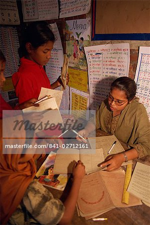 A Bangladeshi woman teacher marks students books in a school in the slums of Dhaka (Dacca), Bangladesh, Asia Stock Photo - Rights-Managed, Image code: 841-02712161