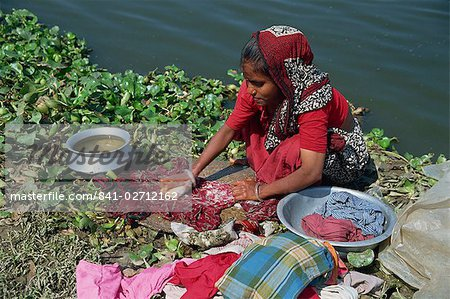 A Bangladeshi woman washing clothes beside the river in Dhaka (Dacca), Bangladesh, Asia Stock Photo - Rights-Managed, Image code: 841-02712162