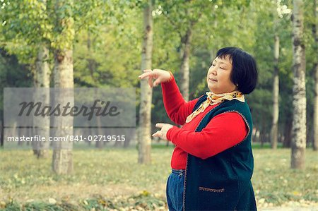 Portrait of a Chinese woman dancing in park, Old Beijing, Beijing, China, Asia Stock Photo - Rights-Managed, Image code: 841-02719515