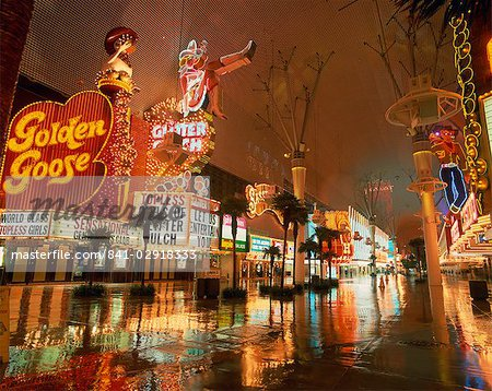Night reflections on wet street of neon signs along Fremont Street in Las Vegas, Nevada, United States of America, North America