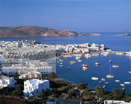 Boats in the harbour and windmills on the coast, with the sea and hills in the background, on Mykonos, Cyclades Islands, Greek Islands, Greece, Europe