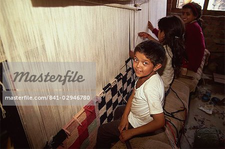 Young children weaving carpets for up to 16 hours a day in carpet factories, Jawlikhel, Kathmandu, Nepal, Asia Stock Photo - Rights-Managed, Image code: 841-02946780