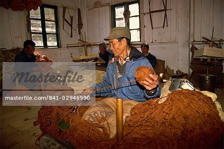 Portrait of a Tibetan man spinning wool in a carpet factory at a self-help centre in Darjeeling, India, Asia Stock Photo - Rights-Managed, Image code: 841-02946990