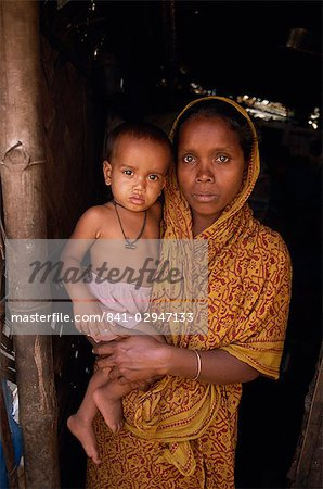 Portrait of a Bangladeshi mother in a sari holding her young child, looking at the camera, in a slum in Dhaka, Bangladesh, Asia Stock Photo - Rights-Managed, Image code: 841-02947133