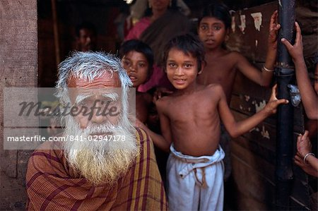Head and shoulders portrait of an old Bangladeshi (Bengali) man with a white beard, and children beyond, looking at the camera, in the slums of Dhaka (Dacca), Bangladesh, Asia Stock Photo - Rights-Managed, Image code: 841-02947178