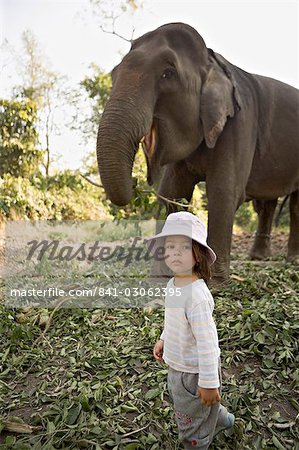 Two year old girl and the elephant that will take her on safari, at the Island Jungle Resort hotel, Royal Chitwan National Park, Terai, Nepal, Asia Stock Photo - Rights-Managed, Image code: 841-03062395