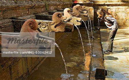 Girl takes a drink from the water spouts in a temple courtyard at Godavari in the south of the Kathmandu valley, Nepal, Asia Stock Photo - Rights-Managed, Image code: 841-03062412