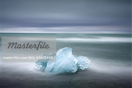 Piece of glacial ice washed ashore by the incoming tide near glacial lagoon at Jokulsarlon, Iceland, Polar Regions Stock Photo - Rights-Managed, Image code: 841-03672449