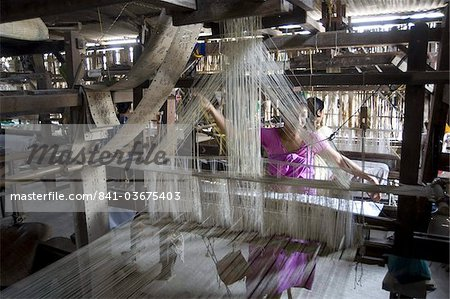 Woman at village silk loom weaving Assam Muga natural undyed silk in Sualkuchi, Assam, India, Asia Stock Photo - Rights-Managed, Image code: 841-03675403
