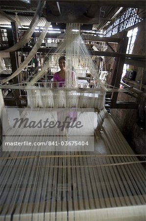 Woman at village silk loom weaving Assam Muga natural undyed silk in Sualkuchi, Assam, India, Asia Stock Photo - Rights-Managed, Image code: 841-03675404