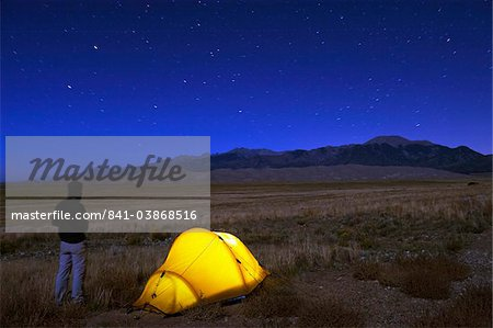 Hiker and tent illuminated under the night sky, Great Sand Dunes National Park, Colorado, United States of America, North America Stock Photo - Rights-Managed, Image code: 841-03868516