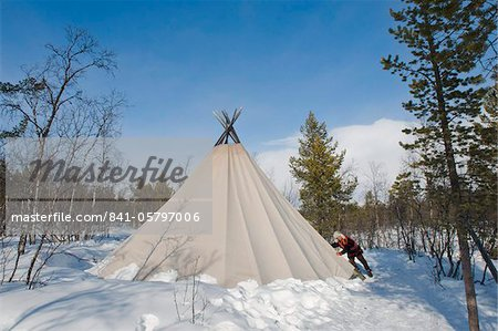Sami man closes the flap on his lavvu tent at his homestead, Kiruna, Lapland, arctic Sweden, Scandinavia, Europe Stock Photo - Rights-Managed, Image code: 841-05797006
