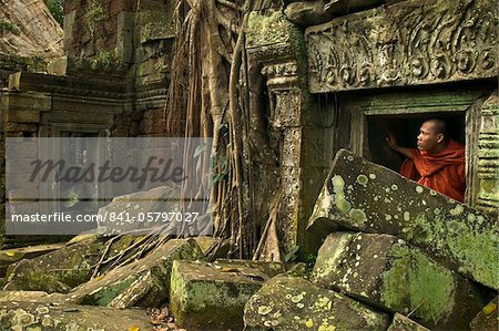 A Buddhist monk peeping out of a window at a jumbled ruin, Ta Prohm temple, Angkor, UNESCO World Heritage Site, Siem Reap, Cambodia, Indochina, Southeast Asia, Asia Stock Photo - Rights-Managed, Image code: 841-05797027