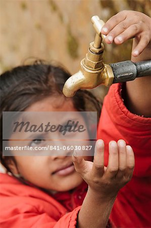Young girl checking to see if the communal village water tap has water, as it runs dry daily, Pokhara, Nepal, Asia Stock Photo - Rights-Managed, Image code: 841-06030827