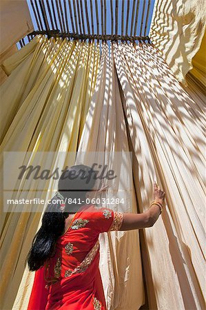 Woman in sari checking the quality of freshly dyed fabric hanging to dry, Sari garment factory, Rajasthan, India, Asia Stock Photo - Rights-Managed, Image code: 841-06031284