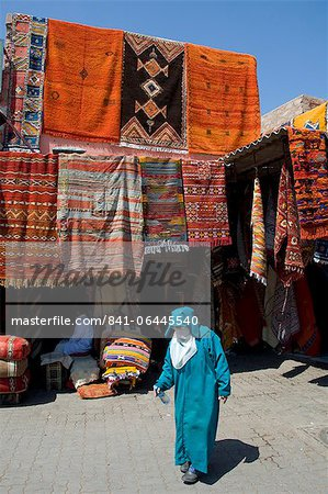 A woman in traditional Islamic dress walking past carpets hanging around an entrance to the souk in Marrakech, Morocco, North Africa, Africa Stock Photo - Rights-Managed, Image code: 841-06445540