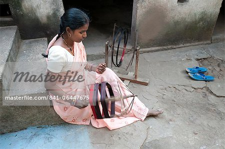 Woman spinning silk thread by hand outside her house, Vaidyanathpur, Orissa, India, Asia Stock Photo - Rights-Managed, Image code: 841-06447675