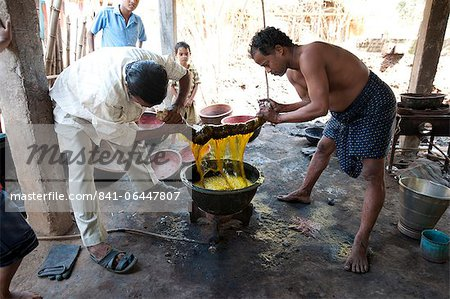 Two men squeezing yellow dye out of cotton fabric over a metal bowl heated over gas flame, Naupatana weaving village, rural Orissa, India, Asia Stock Photo - Rights-Managed, Image code: 841-06447807
