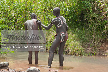 Before the Donga stick fight, the Surma warriors apply a body paint made of clay and mineral on their bodies, Surma tribe, Tulgit, Omo River Valley, Ethiopia, Africa