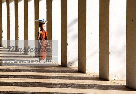 Novice Buddhist monk standing in the shadows of columns at Shwezigon Paya, Nyaung U, Bagan, Myanmar (Burma), Asia Stock Photo - Rights-Managed, Image code: 841-06805720