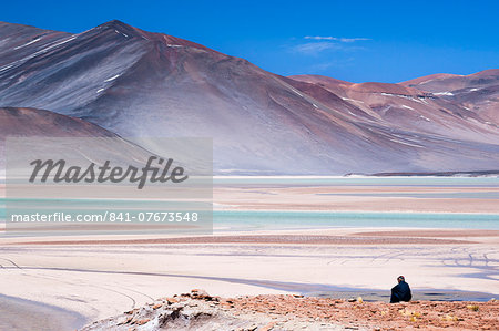 Man sitting on rocks at Miscanti Volcano and high plateau lagoon in San Pedro de Atacama desert, Chile, South America Stock Photo - Rights-Managed, Image code: 841-07673548