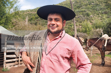 Portrait of a Chilean cowboy (arriero) in a hat on a horse farm in El Toyo region of Cajon del Maipo, Chile, South America Stock Photo - Rights-Managed, Image code: 841-07673552