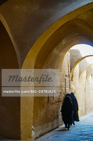 Three women in chadors hurrying down typical vaulted alleyway, Yazd, Iran, Middle East Stock Photo - Rights-Managed, Image code: 841-08781820
