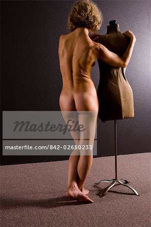 Rear view of young nude woman standing with dressmakers model, studio shot Stock Photo - Rights-Managed, Image code: 842-02650233