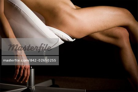 Portrait of young nude woman reclining in chair, close-up studio shot Stock Photo - Rights-Managed, Image code: 842-02650255