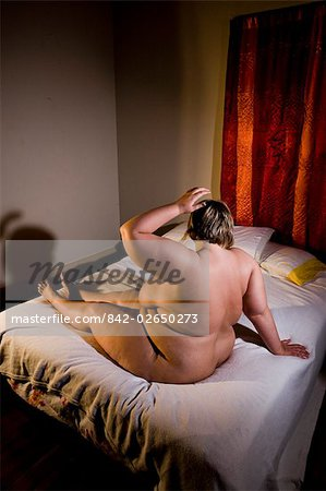 Overweight nude woman sitting on bed in bedroom, side view Stock Photo - Rights-Managed, Image code: 842-02650273