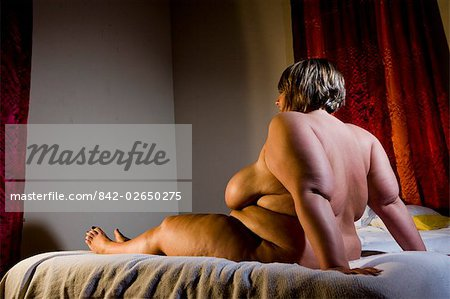 Overweight nude woman sitting on bed in bedroom, side view Stock Photo - Rights-Managed, Image code: 842-02650275