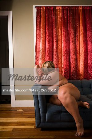 Overweight nude woman sitting on couch in living room, side view Stock Photo - Rights-Managed, Image code: 842-02650312