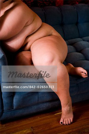 Overweight nude woman sitting on couch in living room, close-up Stock Photo - Rights-Managed, Image code: 842-02650313