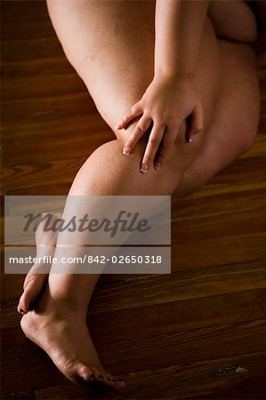 Overweight nude woman lying on hardwood floor, cropped view Stock Photo - Rights-Managed, Image code: 842-02650318