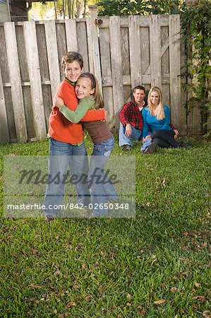 Portrait of young happy family relaxing in the backyard, looking at camera Stock Photo - Rights-Managed, Image code: 842-02650348