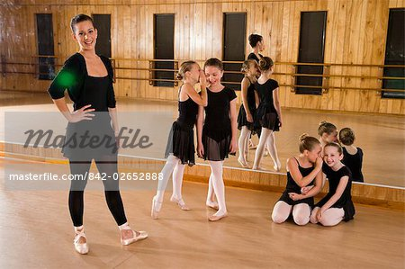 Portrait of ballet girls (8-9) whispering in ears while teacher smiling in foreground in dance studio Stock Photo - Rights-Managed, Image code: 842-02652888