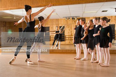 side view of ballet dancers (8-9) practicing while teacher instructing in dance studio with mirror in background Stock Photo - Rights-Managed, Image code: 842-02652906