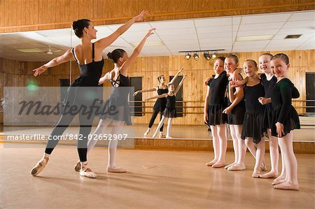 side view of ballet dancers (8-9) practicing while teacher instructing in dance studio with mirror in background Stock Photo - Rights-Managed, Image code: 842-02652907