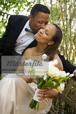 Happy African American groom sitting outside kissing his bride on wedding day Stock Photo - Rights-Managed, Image code: 842-02653401