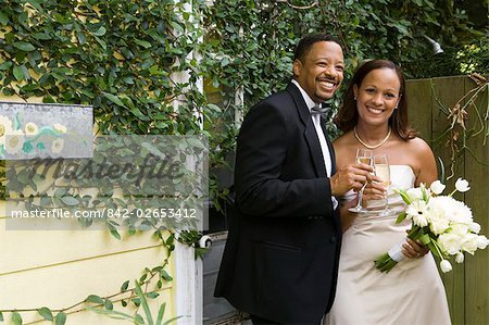 Portrait of happy African American bride and groom toasting champagne glasses outside on wedding day Stock Photo - Rights-Managed, Image code: 842-02653412