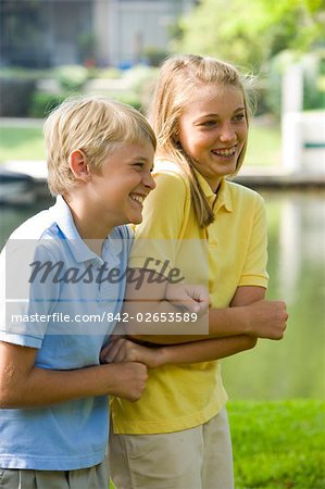 Side view of brother and sister smiling outdoors with lake in background Stock Photo - Rights-Managed, Image code: 842-02653589