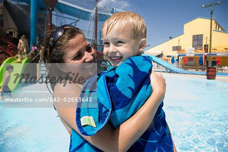 Close-up of mother carrying son wrapped in towel at water park Stock Photo - Rights-Managed, Image code: 842-02653643