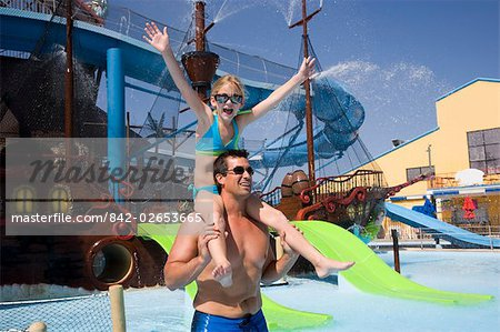 Portrait of father carrying daughter on shoulders at water park Stock Photo - Rights-Managed, Image code: 842-02653665